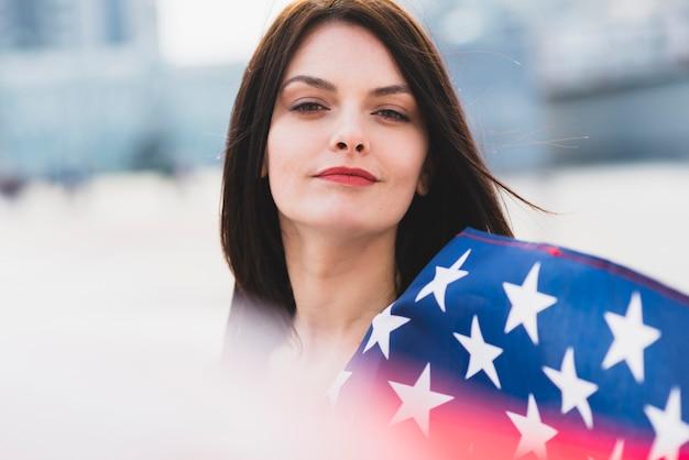 Femme regardant la caméra avec les étoiles blanches du drapeau américain Photo gratuit