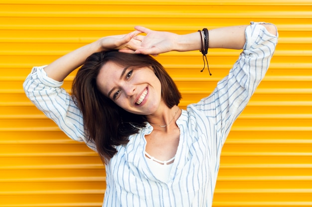 Femme regardant la caméra avec un fond jaune Photo gratuit