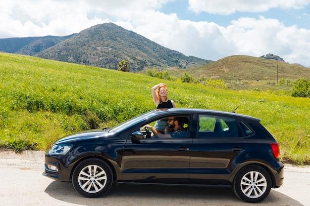 Femme regardant la caméra sortir de la fenêtre de la voiture Photo gratuit