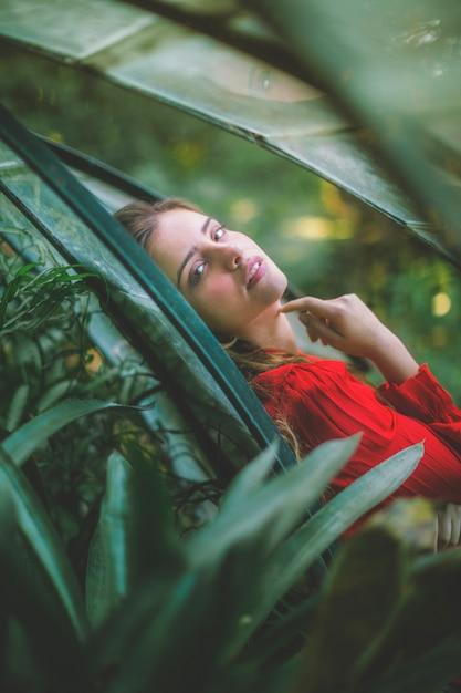 Femme regardant la caméra à travers les plantes Photo gratuit