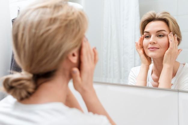 Femme Regardant Dans Le Miroir Et Sourit Photo gratuit