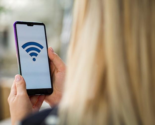 Femme regardant un écran de téléphone avec logo wifi Photo gratuit