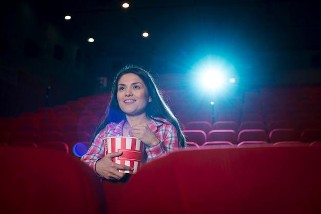 Femme regardant un film au cinéma Photo gratuit