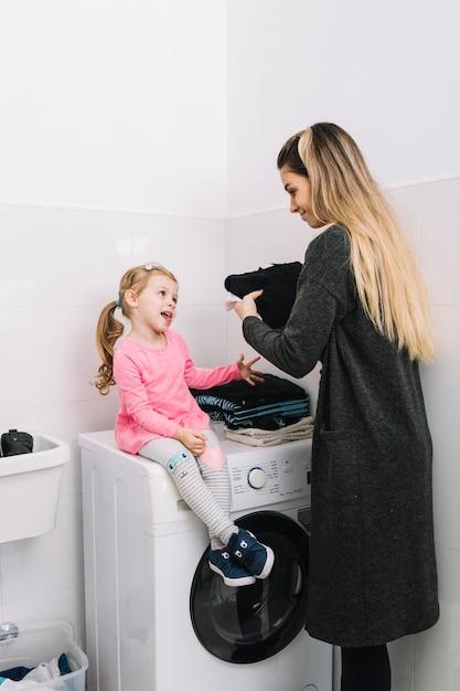 Femme regardant sa fille assise sur une machine à laver Photo gratuit