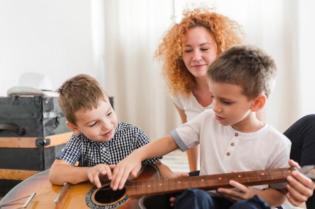 Femme regardant ses enfants jouant de la guitare Photo gratuit