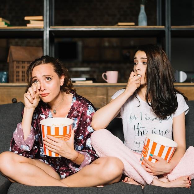 Femme regardant son amie devenir émue en regardant la télévision Photo gratuit