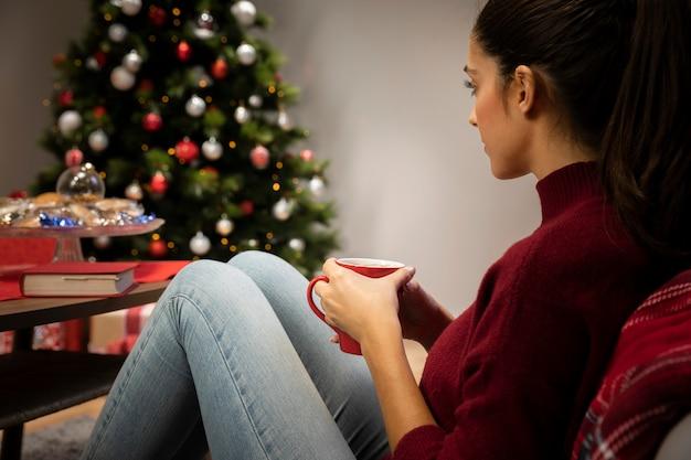 Femme regardant une tasse avec un fond de noël Photo gratuit