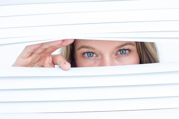 Femme regardant à travers un store Photo Premium