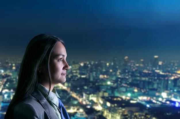 Femme Regardant La Ville De Nuit Photo Premium