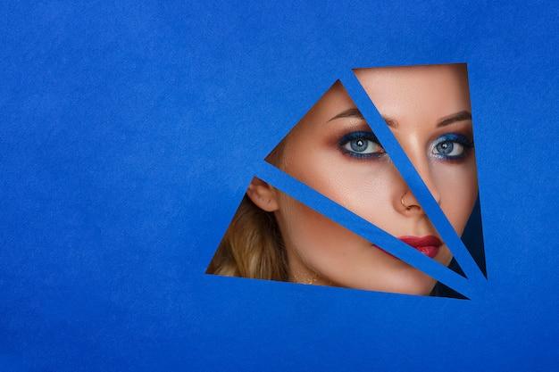 Une femme regarde dans le trou du papier, beau maquillage. Photo Premium
