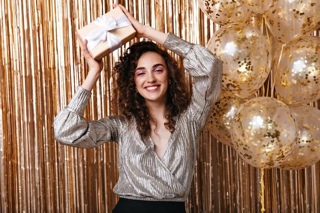 Femme Regarde Joyeusement Dans La Caméra Et Détient Une Boîte Cadeau Photo gratuit