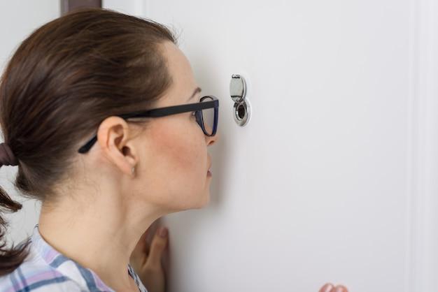 Femme regarde à travers le judas Photo Premium