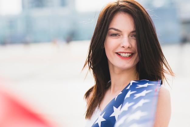 Femme, regarder caméra, et, sourire, agitant, à, étoiles drapeau américain Photo gratuit