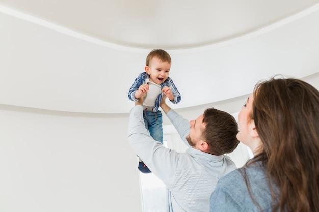 Femme, regarder, mari, porter, bébé, fils, mains Photo gratuit