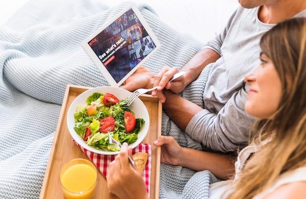 Femme, regarder, série télé, et, manger salade, à, petit ami Photo gratuit
