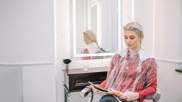 Femme relaxante avec magazine de lecture de colorant appliquée Photo gratuit