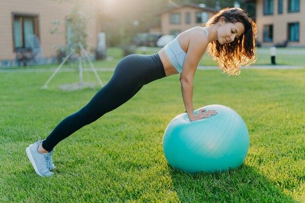 Femme De Remise En Forme Active Fait De La Gymnastique En Plein Air Avec Ballon Gonflé, A Un Entraînement Actif, Photo Premium
