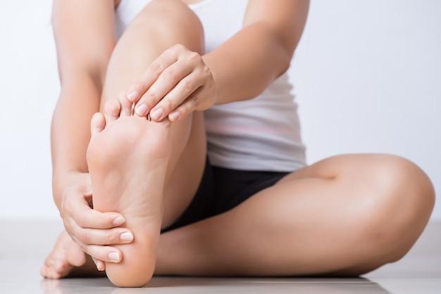 Femme ressentant une douleur au pied à la maison. concept de soins de santé et médical. Photo Premium