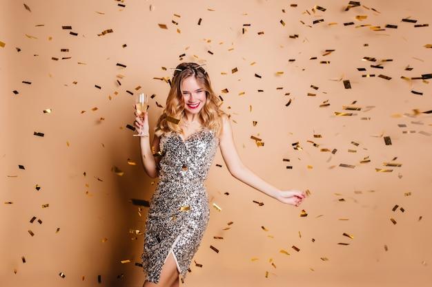 Femme Rêveuse En élégante Robe Scintillante Dansant Avec Verre à Vin Et Souriant Photo gratuit