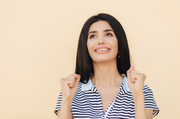 Femme Rêveuse Positive Aux Cheveux Raides Noirs, Garde Les Mains Dans Les Poings Photo Premium