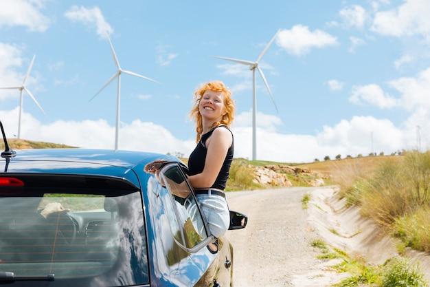 Femme riant et regardant la caméra par la fenêtre de la voiture Photo gratuit
