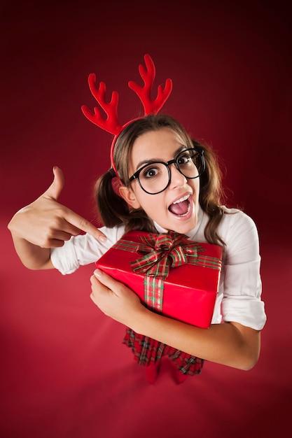 Femme Ringard Choqué Pointant Sur Le Cadeau De Noël Photo gratuit