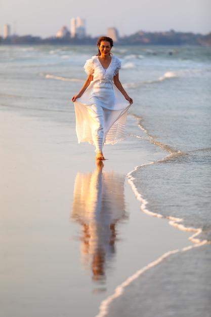 Femme En Robe Blanche Sur La Plage Photo Premium