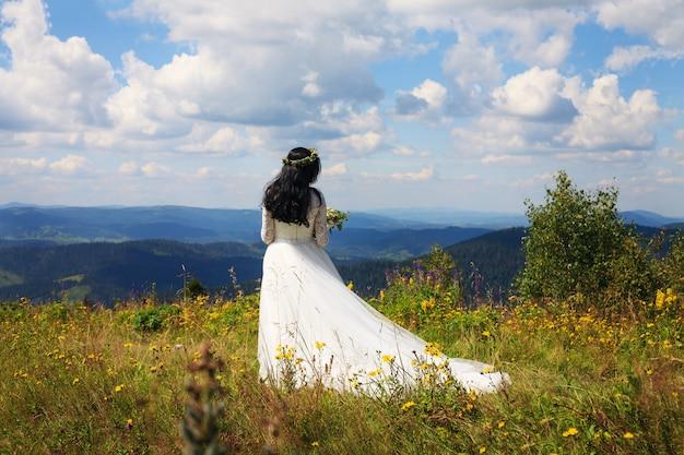 Une femme en robe blanche se promène dans les montagnes. Photo Premium