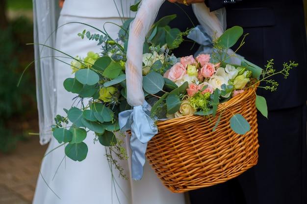 Femme en robe blanche tenant un panier de fleurs sans visage Photo Premium