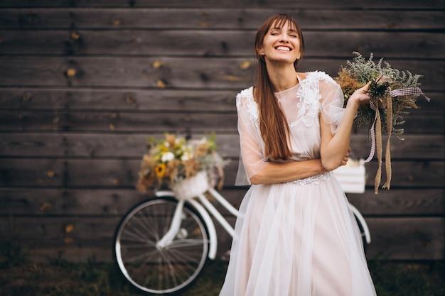 Femme en robe blanche à vélo près du mur en bois Photo gratuit