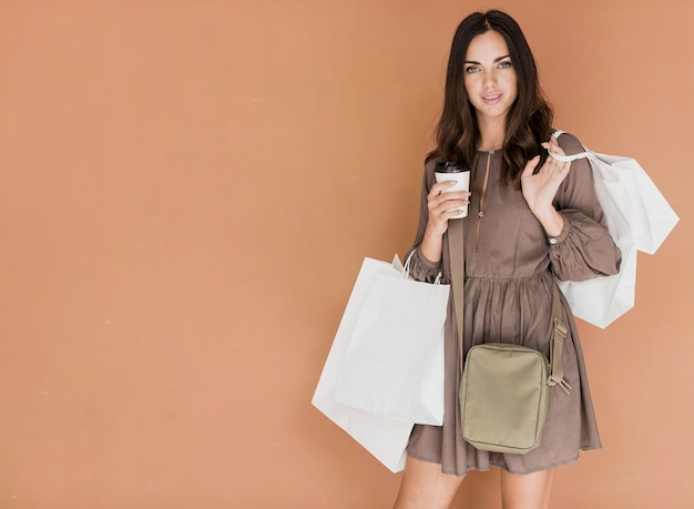 Femme en robe marron avec sac à main et café Photo gratuit