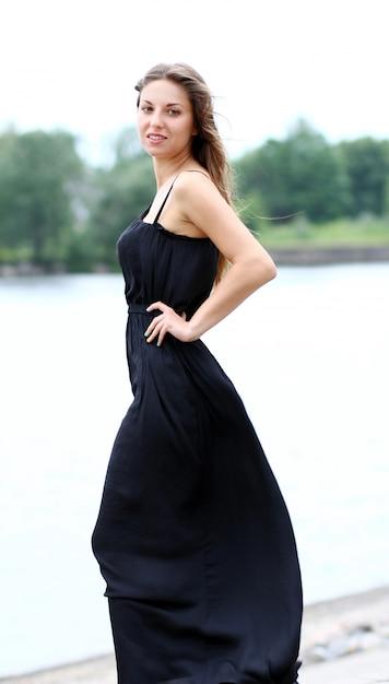 Femme En Robe Noire Au Bord De La Rivière Photo gratuit
