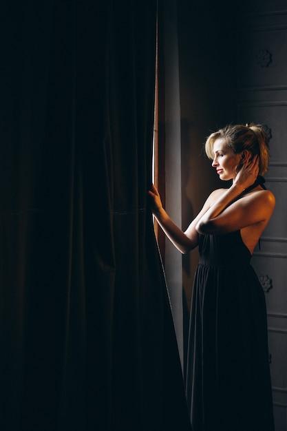 Femme en robe noire debout près de la fenêtre Photo gratuit