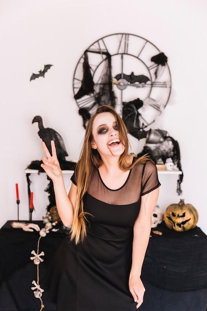 Femme en robe noire devant la composition d'halloween souriant et montrant la paix Photo gratuit