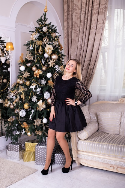 Femme en robe noire près de sapin de noël à la maison Photo Premium
