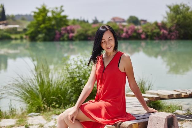 Femme En Robe Rouge Assise Sur Un Banc Photo Premium
