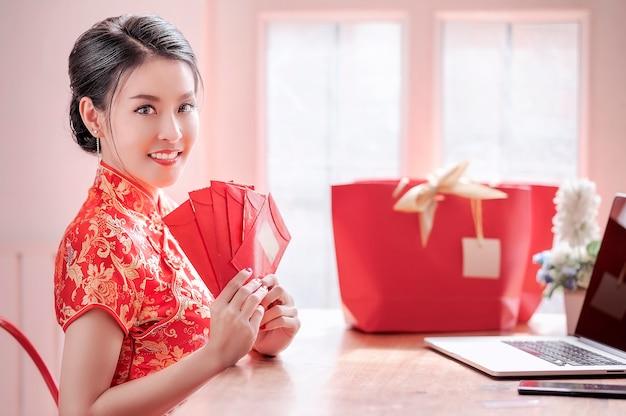 Femme en robe rouge cheongsam traditionnel tenant des enveloppes rouges et utilisant un ordinateur portable Photo Premium