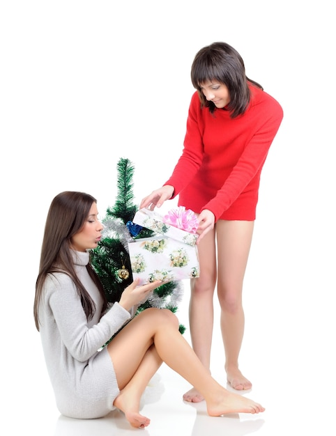 Une Femme En Robe Rouge Est Assise Sur Le Sol Près D'un Arbre De Noël. Fille Dans Une Robe Grise Posant Avec Un Cadeau Dans Ses Mains Photo Premium