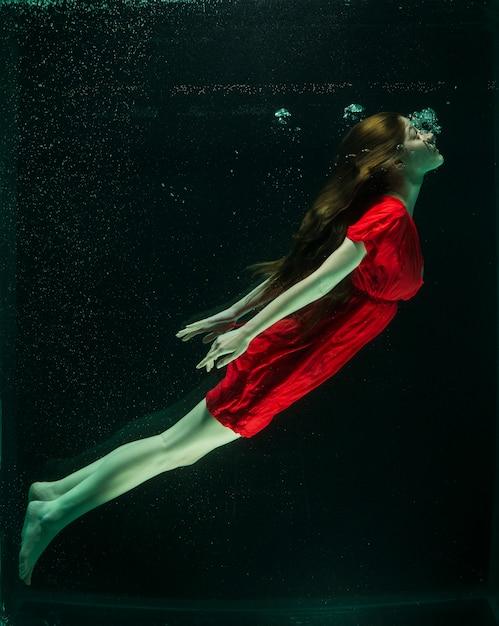 Femme avec robe rouge sous l'eau Photo gratuit
