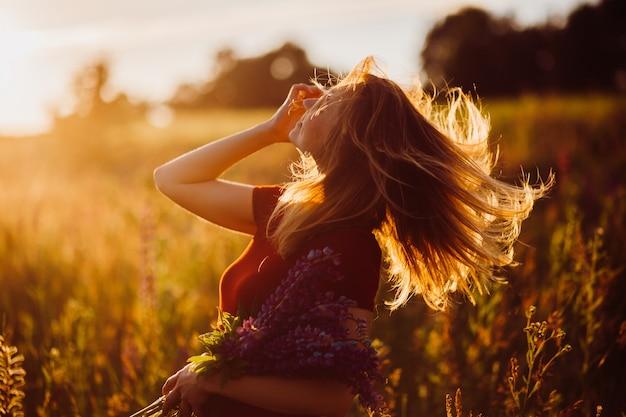Femme en robe rouge tourbillonne dans les rayons du soleil du soir Photo gratuit