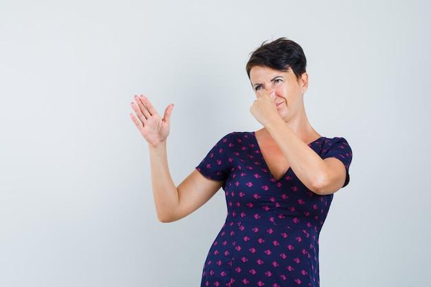 Femme En Robe Se Pinçant Le Nez En Raison D'une Mauvaise Odeur Et à L'air Dégoûté Photo gratuit