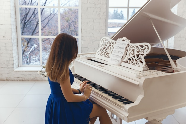 Femme en robe de soirée bleue jouant sur un piano blanc Photo Premium