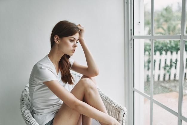 Femme Romantique Près De La Fenêtre Est Assise Sur Une Chaise à L'intérieur Photo Premium