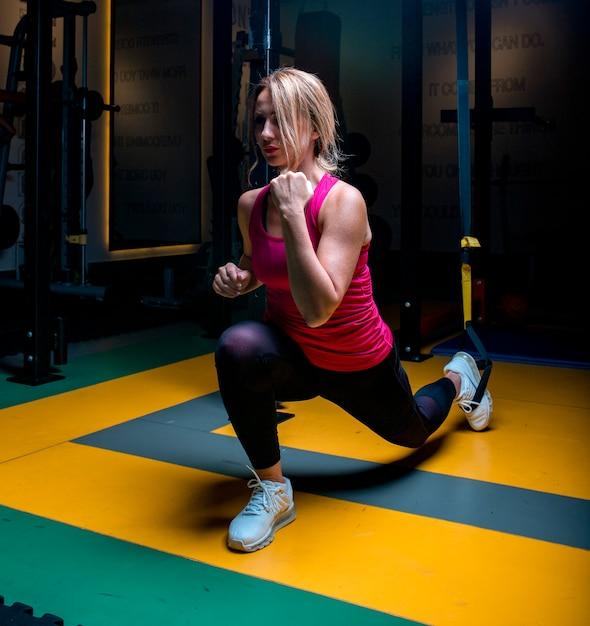 Femme en rose faisant des activités d'échauffement et d'étirement dans une salle de sport. Photo gratuit