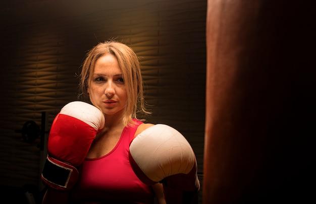 Femme en rose avec des gants de boxe, entraînement avec sac de boxe. Photo gratuit
