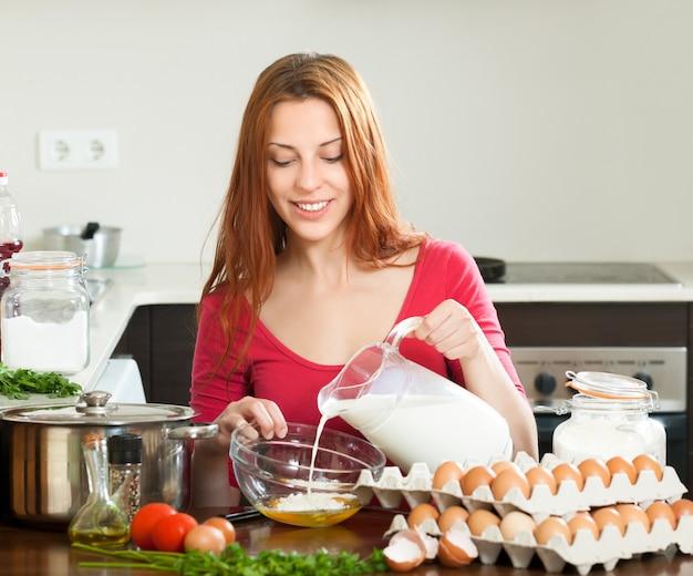 Femme en rouge faisant de la pâte ou de l'omlet dans la cuisine Photo gratuit