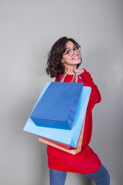 Femme en rouge avec des sacs à provisions dans le dos Photo gratuit