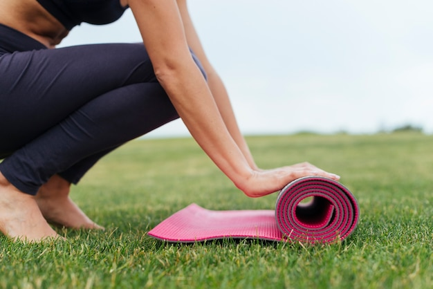 Femme roulant tapis de yoga en plein air Photo gratuit