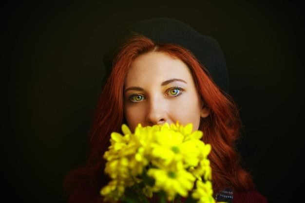 Femme rousse française au béret noir tient et renifle des chrysanthèmes jaunes Photo Premium