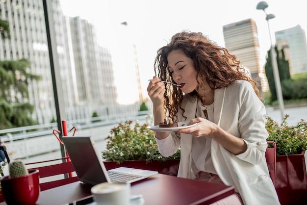 Femme Rousse Jeune Entreprise Sur L'ordinateur Et Manger Un Gâteau Photo Premium